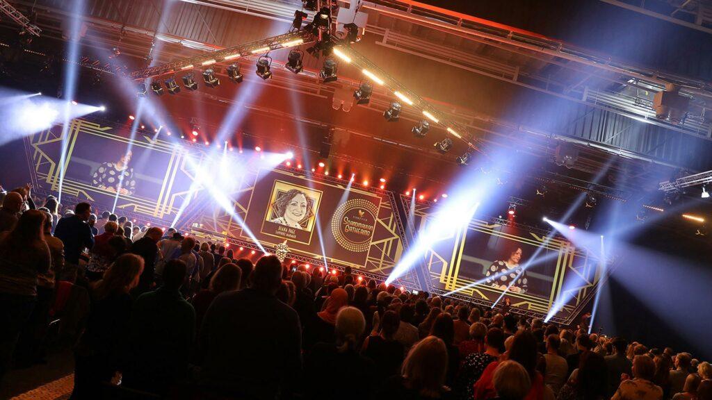 Fysiskt event där många människor tittar på person på scen